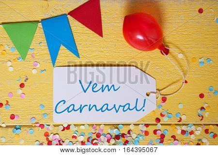White Label With Spanish Text Vem Carnaval Means Happy Carnival. Party Decoration Like Streamer, Confetti And Balloon. Flat Lay Or Top View. Yellow Wooden Background