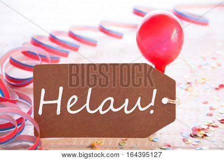 One Label With German Text Helau Means Happy Carnival. Party Decoration Like Streamer, Confetti And Balloon. Wooden Background With Vintage, Retro Or Rustic Syle