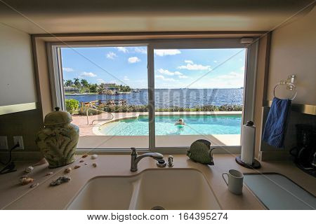 Looking through a window to a pool area with woman in the pool