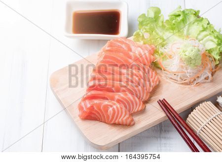 salmon sashimi on wood block and white wood background Japaness food concept healthy food and diet