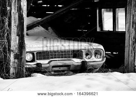 Front end of vintage car with broken headlights in a wood structure shed in winter black and white