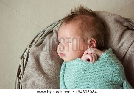 Newborn baby with a Mohawk hairstyle is sleeping in the basket