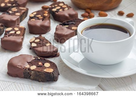 Homemade dark chocolate biscotti cookies with almonds covered with melted chocolate and cup of coffee horizontal