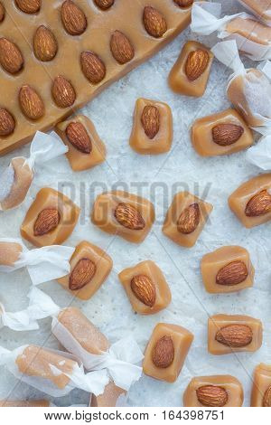 Homemade soft caramel candy with almonds vertical top view