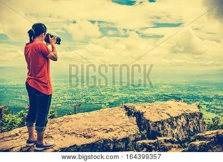 Asian woman photographed the beautiful view by digital camera at tropical evergreen forest. Pretty sky with cloudy outdoor at the daytime on summer day. Vintage tone effect.