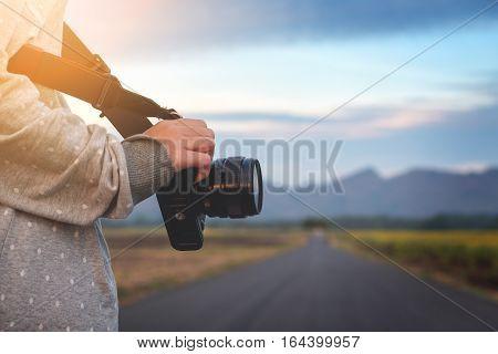 Female hand holding camera ready to take photo