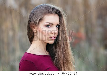 Portrait of pensive sad lonely innocent Caucasian Russian blonde young beautiful woman girl with long hair outside looking in camera autumn fall summer shoot