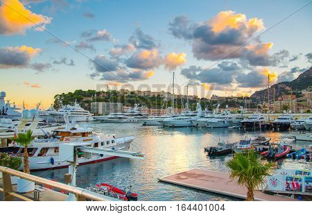 Monaco, Monte Carlo - September 16, 2016: Sunset in Principality of Monaco. View of the seaport and the city of Monte Carlo with luxury yachts and sail boats