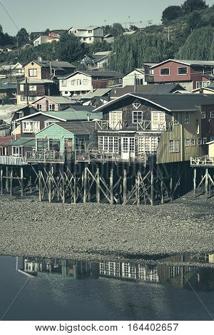 Colorful Palafitos traditional wooden stilt houses at low tide in Castro the capital of the Chiloe Archipelago in Chile (Digitally Altered: Toned Image)