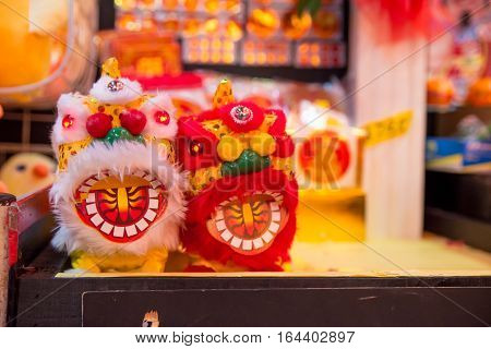 Close-up detail of two dancing lion toys with their mouths open on sale during the Chinese New Year festival in Singapore. Travel and holidays concept.