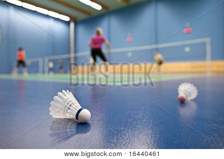 badminton - badminton courts with players competing; shuttlecocks in the foreground (shallow DOF; color toned image)