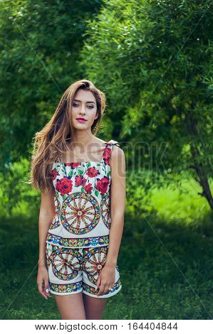 Portrait of young beautiful woman wearing trendy summer outfit posing in park. Professional make-up and hairstyle. Perfect skin. Fashion photo.