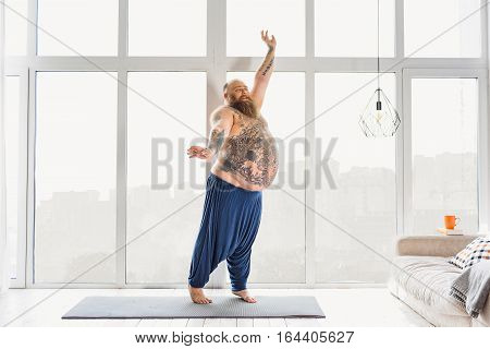 What a wonderful morning. Joyful fat man is standing on sport mat and stretching arms sideways. He is smiling with happiness