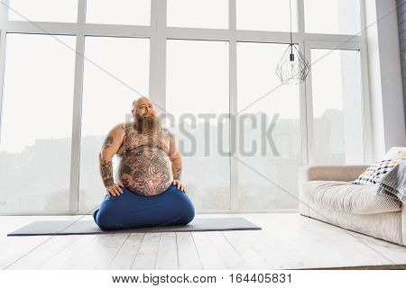 Lazy mature male fatso is ready to exercise. He is sitting on sport mat in living room and smiling