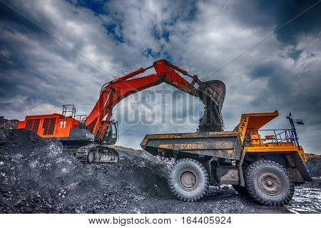 NOVOKUZNETSK, RUSSIA - JULY 26, 2016: Big yellow mining trucks and excavators at worksite