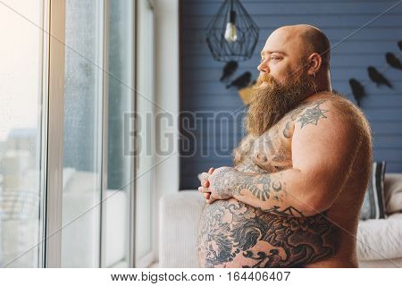 Pensive mature thick guy is looking through window with sadness. He is toughing his big tattooed abdomen