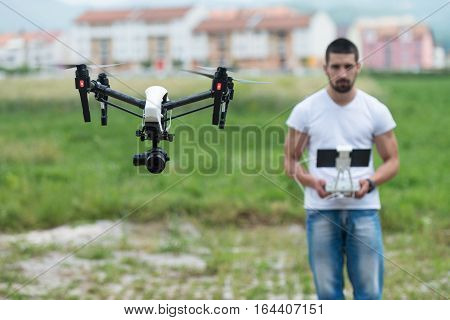 Man Outdoors With Remote Control Flying A Drone