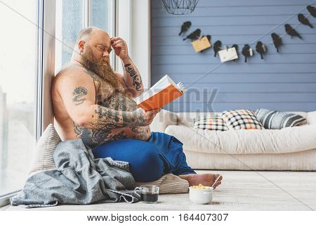 Mature thick guy is trying to understand literature. He is touching his forehead pensively. Fatso is sitting on floor near cup of coffee and bowl of cereals