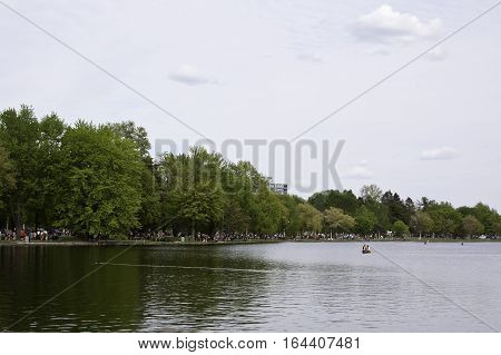Ottawa, Ontario, September 28, 2016 - Wide landscape image of canoes on the Rideau Canal with trees along the left shore on a bright sunny day in May at the Tulip Festival in Ottawa Ontario.