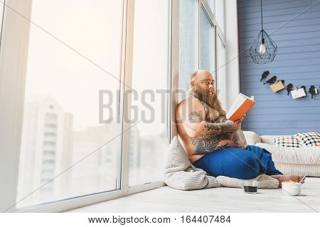 Joyful male fatso is reading book with interest. He is looking at camera and smiling