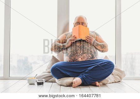 Mature thick guy is scared after reading book. He is hiding behind pages and staring at camera with shock. Fatso is sitting on floor near cup of coffee and cereals