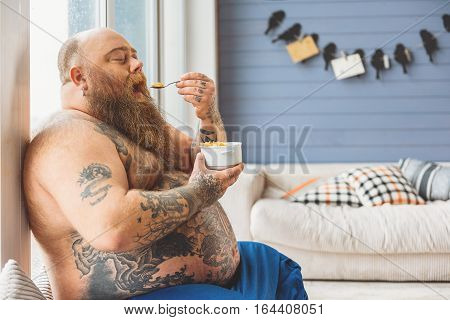 Hungry at man is eating cereals at home. His eyes are closed with enjoyment