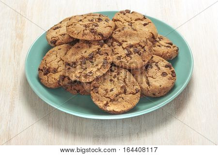 A photo of chocolate chips cookies on a teal plate, shot on a light wooden background texture, with copyspace