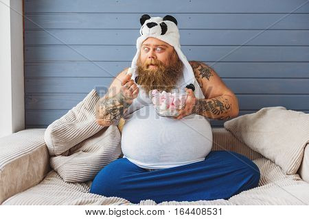 Hungry fat man is looking at zephyr with appetite. He is relaxing on sofa at home in funny panda hat