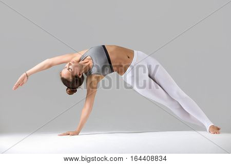 Young attractive woman practicing yoga, stretching in Bending Side Plank exercise, Vasisthasana pose, working out wearing sportswear, indoor full length, isolated against grey studio background