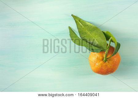 A photo of a vibrant orange tangerine with green leaves, shot from above on a light background texture with copyspace