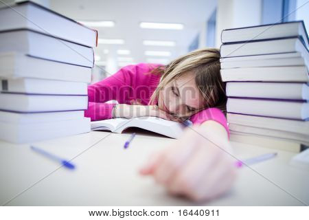 in the library - very tired/exhausted, pretty, female student with books working in a high school library (color toned image)