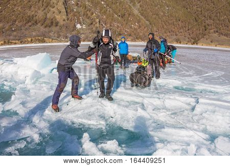 Lake Baikal, Russia - March 24, 2016: The Men Dragged The Ice Sledge Through A Crack In The Ice Of L