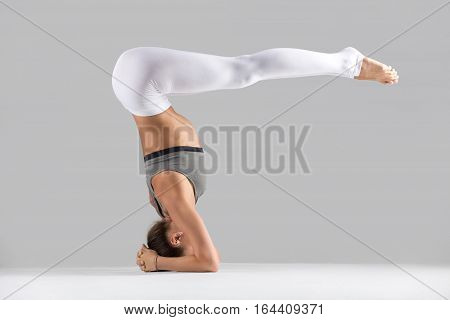 Young attractive woman practicing yoga, standing in headstand exercise, variation of salamba sirsasana pose, working out wearing sportswear, indoor full length, isolated, grey studio background
