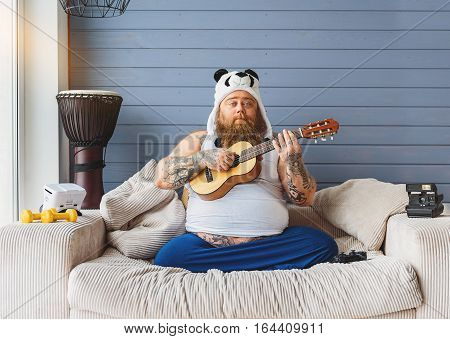 Carefree fat man is playing guitar with enjoyment. He is sitting on sofa at home