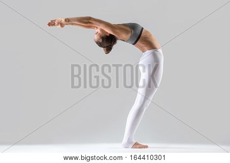 Young attractive woman practicing yoga, doing Standing Backward Bend exercise, Ardha Chakrasana pose, working out wearing sportswear, indoor full length, isolated, grey studio background