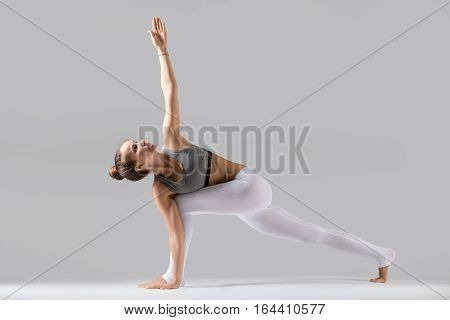 Young attractive woman practicing yoga, standing in Revolved Side Angle exercise, Parivrtta Parsvakonasana pose, working out wearing sportswear, indoor full length, isolated, grey studio background