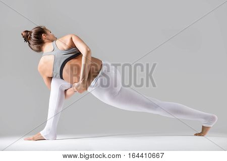 Attractive woman practicing yoga, standing in Revolved Bound Side Angle exercise, Parivrtta Parsvakonasana pose, working out wearing sportswear, indoor full length, grey studio background, rear view