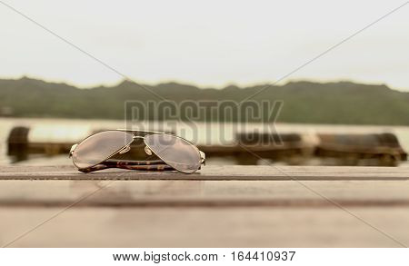 Sun glasses Placed on a wooden floor and Mountain river sky sun vintage color styles
