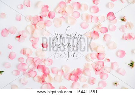Be bright. Be happy. Be you. Inspirational quote made with calligraphy and floral pattern with pink rose petals. Flat lay top view