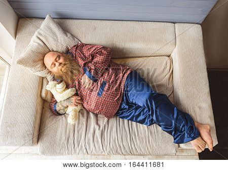 Sweet dreams. Innocent fat man is sleeping on sofa while hugging teddy bear