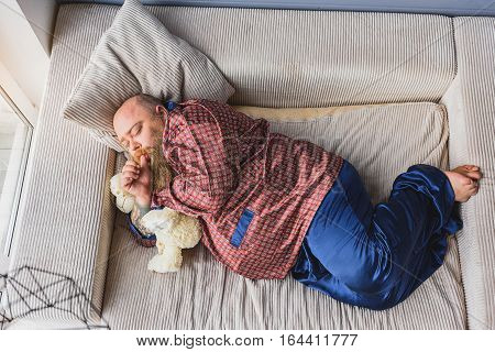 Sleeping as bear. Calm thick man is napping on couch with soft toy. He is lying and sucking his finger