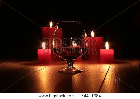 glass of cognac and red candle on a wooden background
