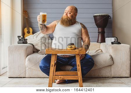 Beer is good. Joyful thick guy is drinking lager at home. He is sitting on couch and looking at glass with proud