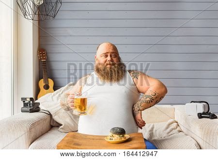 Male fatso is drinking beer with junk food at home. He is sitting on sofa and looking at camera with confidence