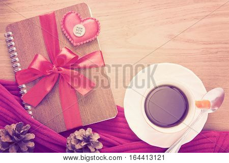 notebook wrapped with red ribbon red felt hearts with Made With Love medal on top and cup of coffee in vintage pink color tone all on wooden table good for valentine or special occasion