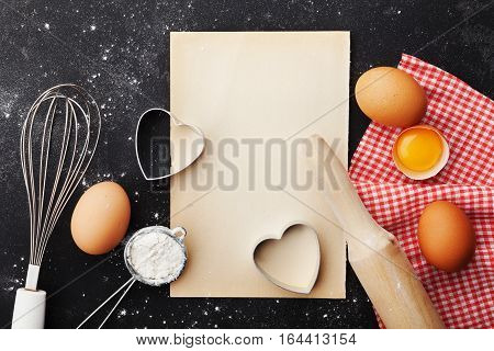 Baking background with flour, rolling pin, eggs, paper sheet and heart shape top view for Valentines day cooking. Flat lay style.
