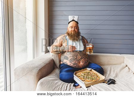 Funny fat man is drinking beer with pizza. He is sitting on sofa and touching his large abdomen with satisfaction. Heavy eater is holding virtual reality device on head
