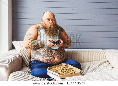 Thick guy is playing console with aspiration. He is sitting on couch near unhealthy food