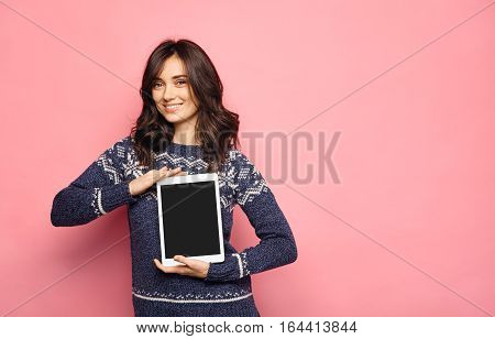 Pretty smiling woman showing black screen of digital tablet. Young brunette wearing winter sweater and holding tablet over pink color background with copy space