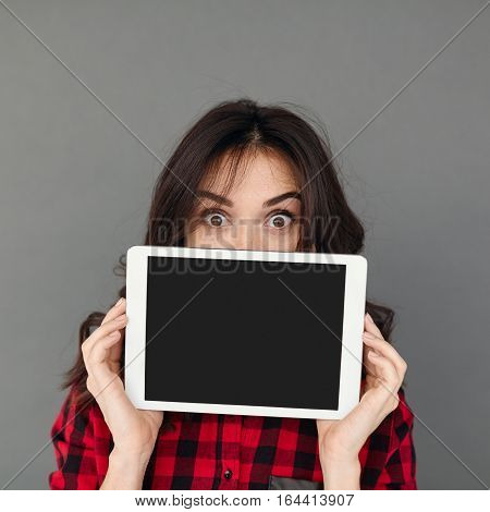 Close-up young brunette woman showing empty black Tablet screen over grey background